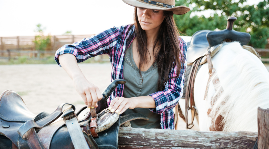 Woman adjusting horse saddle
