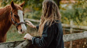 Woman petting horse in corral