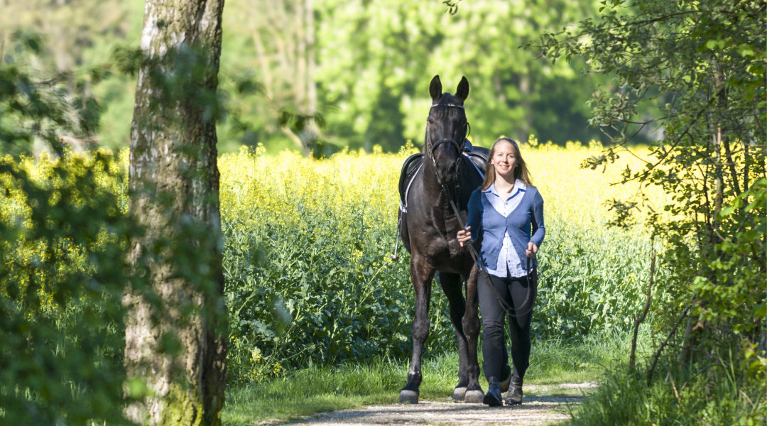 woman walking horse in field