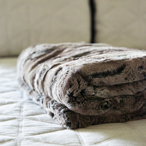 Super soft and comfy faux fur throw blanket folded up on a bed in a master bedroom.