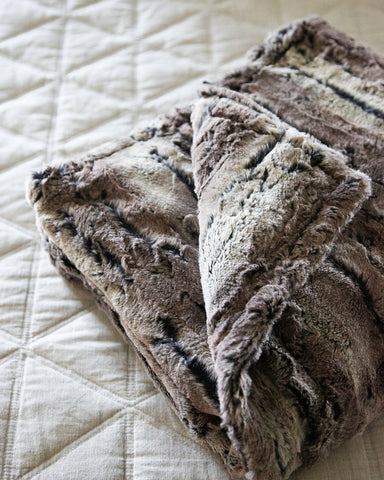 Super soft and comfortable neutral faux fur throw blanket folded on a bed in a master bedroom