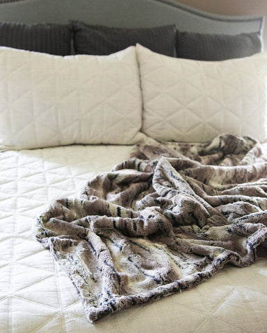 Soft and comfortable faux fur 50x60 standard size throw blanket thrown on a bed in a master bedroom with a white comforter.