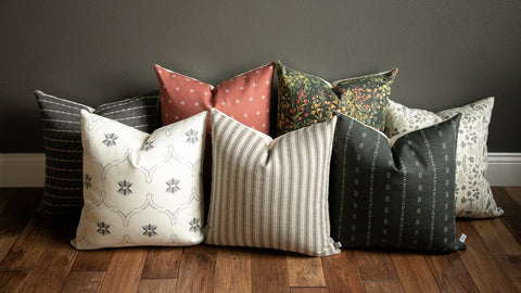 fall 2021 throw pillow combo shown in a rust pillow, floral pillow, black pillow, rich warm color palette