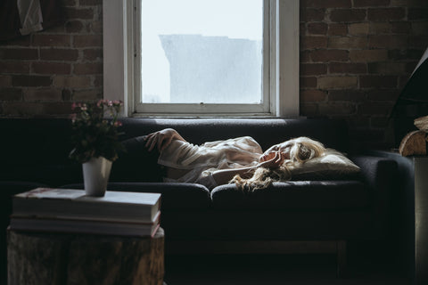 Woman lounging on the couch sad