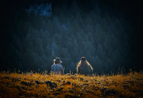 two friends sitting in a field