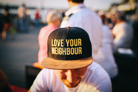 "Man wearing a hat that says ""love your neighbour"""