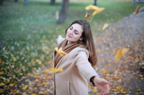 Woman enjoying the leaves falling in Autumn