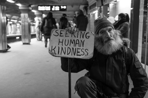 homeless man holding a seeking kindness sign