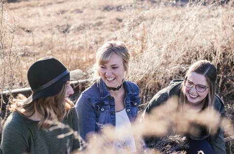 friends laughing together in a field