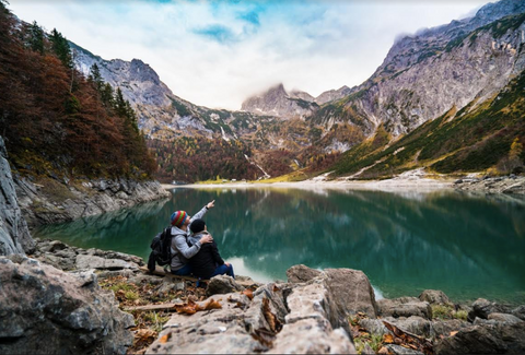A couple sitting next to a beautiful lake