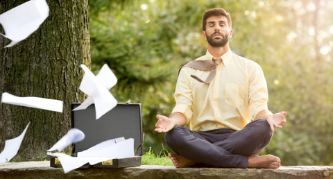 man sitting in meditation pose in work clothes