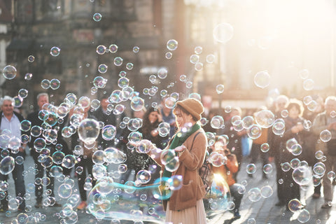 Girl blowing bubbles in the city