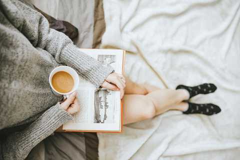Woman lounging, drinking tea and reading a book