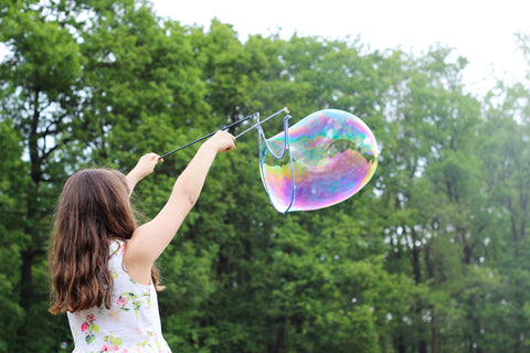 Little girl playing with bubbles
