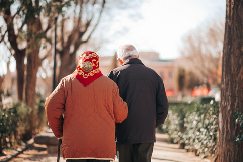 Elderly couple walking arm in arm