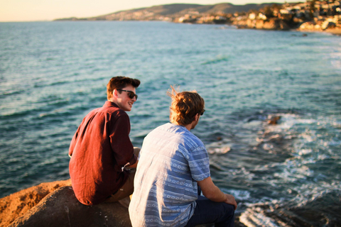 Two male friends chatting on a rock near the ocean