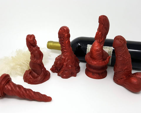 A collection of Lust Arts toys (Unicorn Horn, Mermaid, Mosswood Dragon, Lust Burster on a Double-Sided Suction Cup, and a Frank's Monster) with a red wine bottle and a piece of fur on a white background