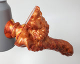 Mosswood Dragon dildo seen from the side in color Fiery Maple held on to a soda can with a Medium/Medium Double-Sided Suction Cup in matching Fiery Maple color