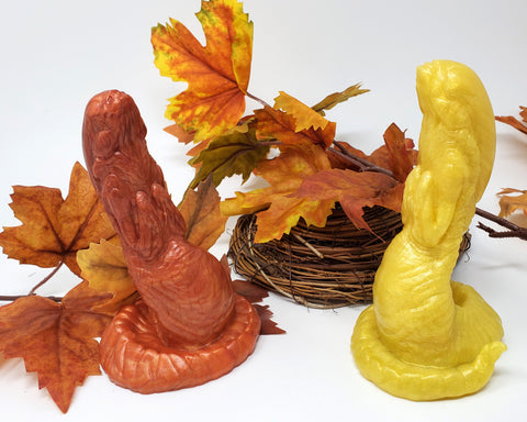 Two Lust Burster adult toys on a white background next to silk maple leaves and a nest-like coil of twigs and wood