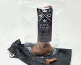 Packaged King Noire adult toy standing up on a black satin bag with a mini charm toy on a white background