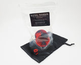 A packaged King Noire Double-Sided Suction Cup and mini charm version on a small black satin bag on a white background