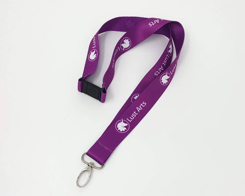 Photo of a medium-dark purple lanyard with the Lust Arts logo in white with a silver hook on an off-white background