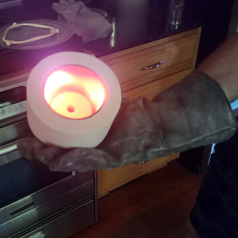 a gloved hand holding a glowing hot microwave kiln lid