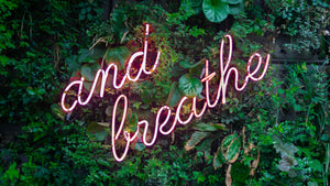 neon sign breathe on green wall
