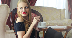Picture of woman holding a cup of tea while smiling