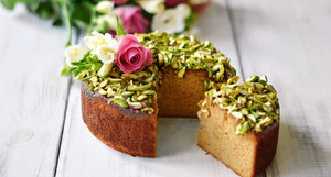 A cake with dry fruit and flower on top