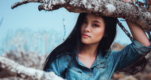 Picture of woman in blue shirt posing under a barren tree
