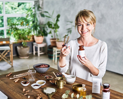 Picture of woman holding flower and spice product in hand