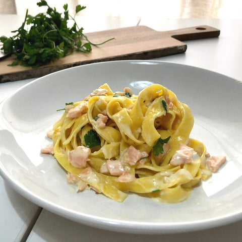 Creamy salmon tagliatelle with parsley in the background - pasta evangelists