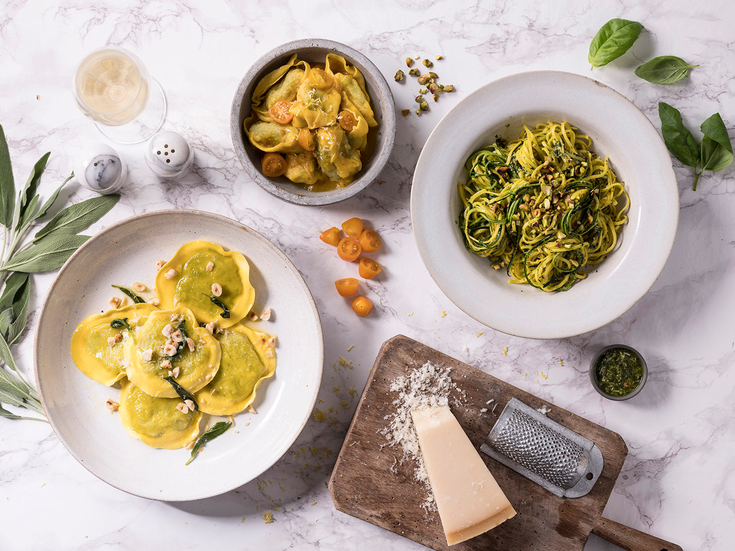 selection of girasoli pasta, tortelloni pasta and courgetti pasta with parmesan, tomatoe and hazelnut garnishes