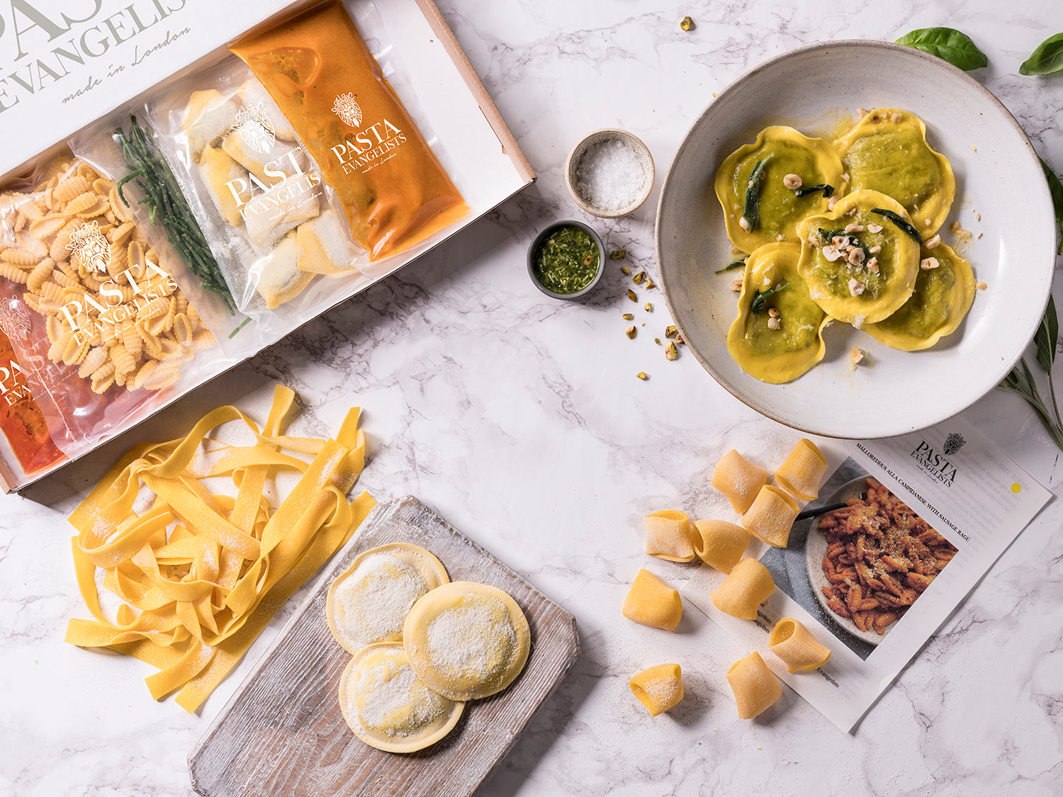 pasta evangelists box with a selection of dishes in packaging, on the side a cooked dish of girasoli pasta as well as uncooked ravioli, paccheri and pappardelle pastas