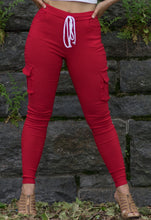 Red women's soft cargo pants with side pockets on both legs.