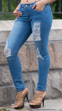Women's blue skinny ripped denim jeans.