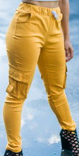 Yellow women's soft cargo pants with side pockets on both legs.