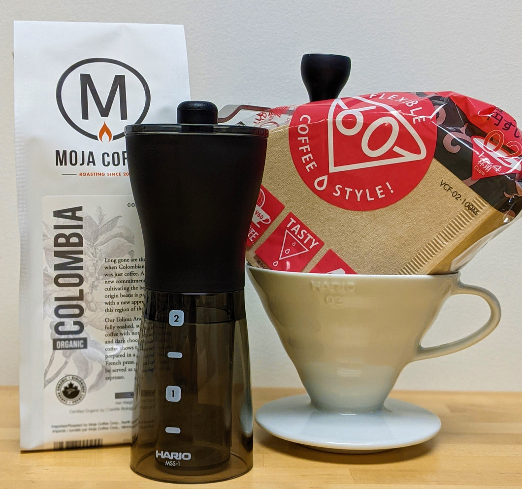 A bag of Moja Coffee's Colombia Medium Roast, a Hario Slim Grinder, Hario V60 Pour Over in Ceramic, as well as a bundle of Hario V60 Filters on a wooden tabletop with a white background.