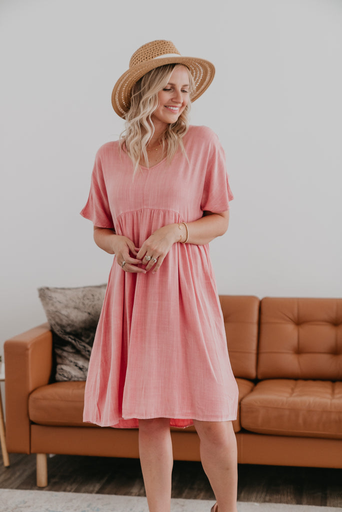 The Anniston Babydoll Dress, lightweight, babydoll dress, modest, comfortable, V-neckline, raglan sleeves, pockets, hi-low hem, dress, relaxed fit, Baby Bump Friendly, knee length, mauve, pink, summer dress, women's fashion