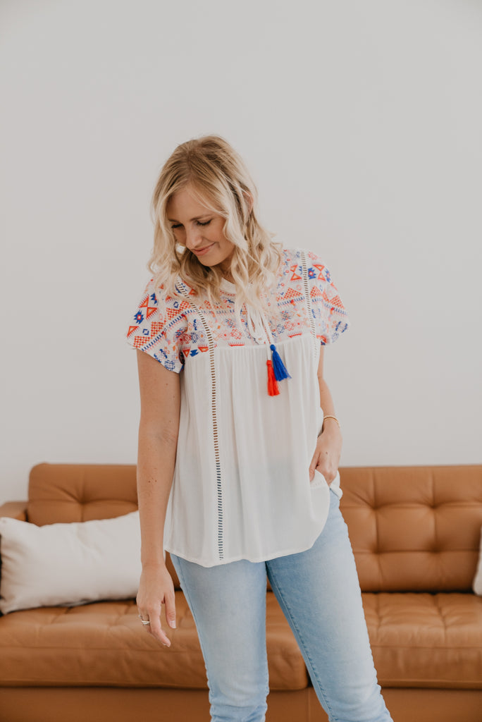 The Alora Embroidered Top in Ivory, relaxed fit, tassel tie neck, cap sleeves, embroidery in Red, White & Blue , summer top, crochet detail, short sleeves, Baby Bump Friendly