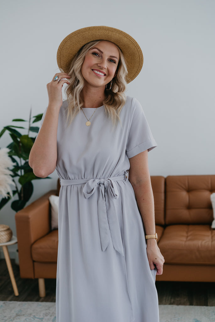 The Giselle Faux Wrap Dress in Light Gray, Wren & Ivory dresses, fashion, Wren & Ivory, Wren and Ivory, short cuff sleeve, faux wrap dress, maxi length, solid light gray dress, modest dress, round neckline, ladies dress, elastic waist with self tie belt, bridesmaid dress
