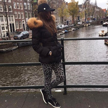 A photo of a customer wearing the Attentif Paris Black Parka coat standing on a bridge