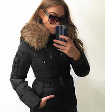 A selfie in the mirror of a customer wearing the Attentif Paris Black Parka Jacket showing off the raccoon fur lined hood