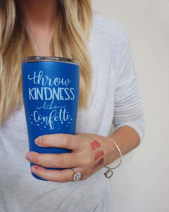 woman holding dark blue tumbler cup with white writing that says throw kindness like confetti in a mix of cursive and print,with confetti at the bottom