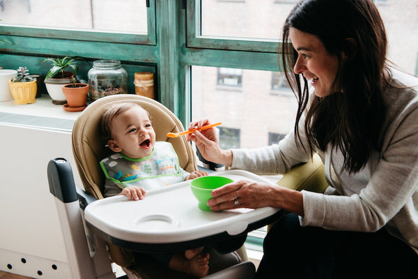 mom feeding smiling baby in high chair