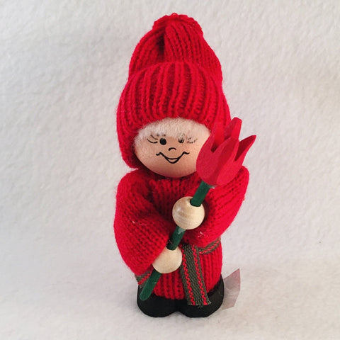 Swedish tomte holding a red tulip