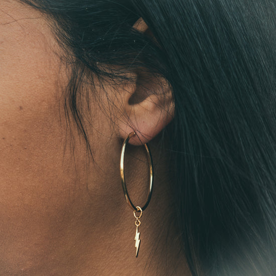 made of lightning earring charm on midi hoop base 14k gold