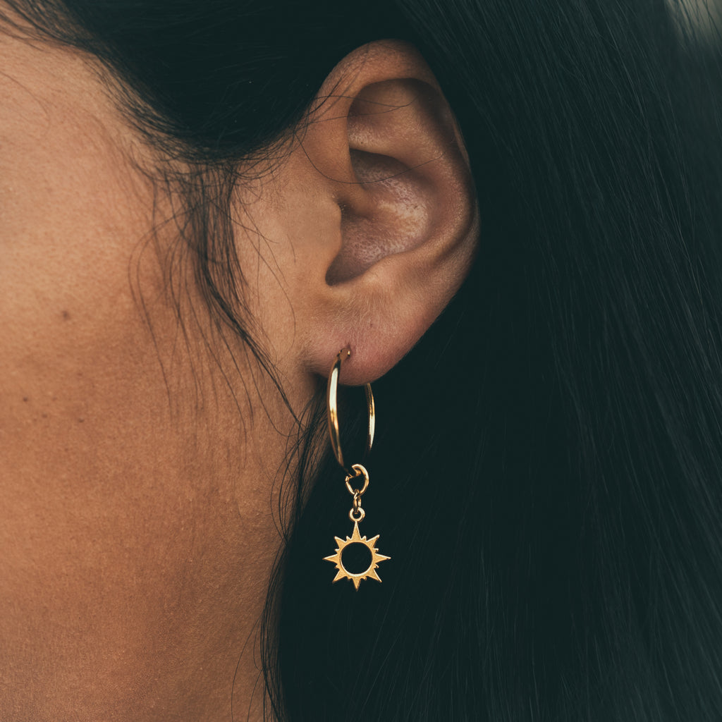 bryan anthonys sun will rise earring charm 14k gold paired with mini hoop earring base close-up on model