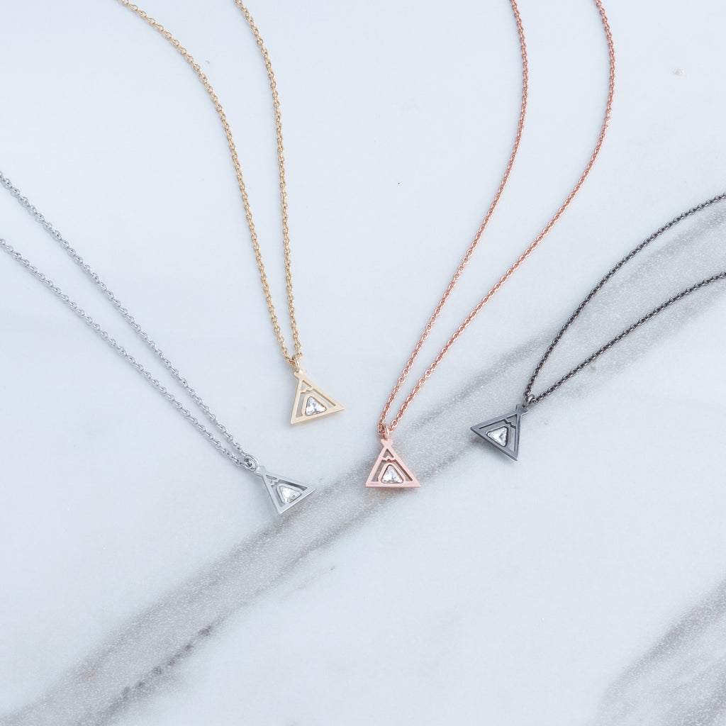 Bryan Anthonys tribe teepee necklace dainty 14k gold rose gold silver and gunmetal on marble